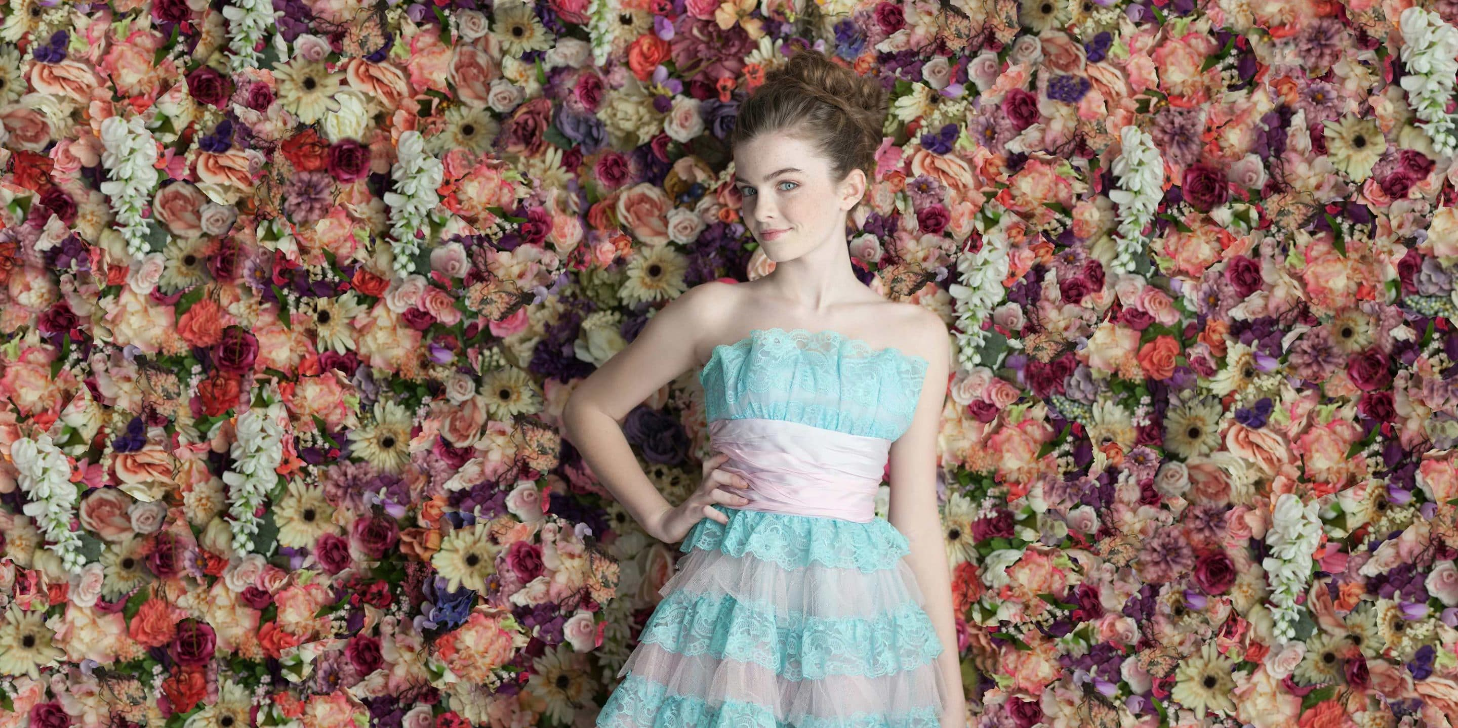 Senior portrait in blue dress with flowers in background